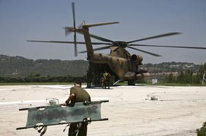 An Israeli soldier carries a blood-stained stretcher back to an Israeli army helicopter