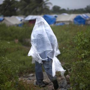 A man who survived the Haiti earthquake covers up with a plastic bag as tropical storm Tomas nears (AP)