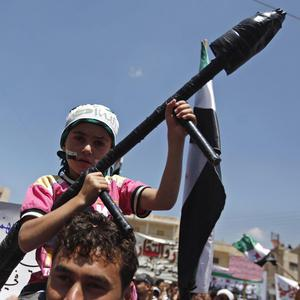 A Syrian boy carries a toy rocket launcher during a protest on the outskirts of Idlib, Syria (AP)
