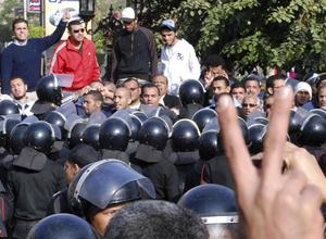 Egyptian protestors flash V sign as anti-riot policemen surround a protest in Suez, Egypt, Thursday, Jan. 27, 2011. Egyptian activists protested for a third day as social networking sites called for a mass rally in the capital Cairo after Friday prayers, keeping up the momentum of the country's largest anti-government protests in years. (AP Photo)