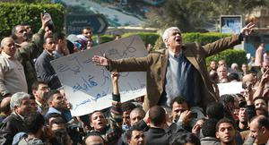 CAIRO, EGYPT - JANUARY 30:  A man gestures as he speaks to protestors in Tahrir Square on January 30, 2011 in Cairo, Egypt. As President Mubarak struggles to regain control after five days of protests he has appointed Omar Suleiman as vice-president. The present death toll stands at 100 and up to 2,000 people are thought to have been injured during the clashes which started last Tuesday. Overnight it was reported that thousands of inmates from the Wadi Naturn prison had escaped and that Egyptians were forming vigilante groups in order to protect their homes after Police were nowhere to be seen on the streets.  Broadcasts from the Al-Jazeera television network via an Egyptian satellite have now been halted.  (Photo by Peter Macdiarmid/Getty Images)