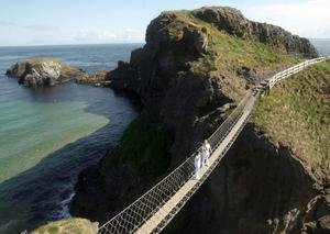 Torchbearer Denis Broderick passing the Olympic flame to Clare Leahy on the Carrick-a-Rede bridge