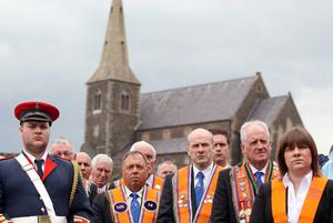 Press Eye - Belfast - Northern Ireland - 10th July 2011 - Picture by Jonathan Porter/ PressEye.com -  Annual Drumcree Orange Order parade in Portadown.  The parade is stopped outside Drumcree Church from going down the mainly nationalist Garvaghy Road.  Orange men pictured at the barrier with Drumcree Church in the background.