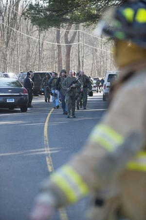 NEWTOWN, CT - DECEMBER 14:  Connecticut State Police walk on Dickson Street  from the scene of an elementary school shooting on December 14, 2012 in Newtown, Connecticut. According to reports, there are about 27 dead, 18 children, after a gunman opened fire in at the Sandy Hook Elementary School. The shooter was also killed.  (Photo by Douglas Healey/Getty Images)