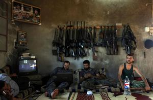 Free Syrian Army fighters sit in a house on the outskirts of Aleppo, Syria, Tuesday, June 12, 2012.  On Tuesday, Syrian forces pelted the eastern city of Deir el-Zour with mortars as anti-government protesters were dispersing before dawn Tuesday, killing several people, activists said. The offensives were part of an escalation of violence in recent weeks that has brought more international pressure on President Bashar Assad's regime faces over its brutal tactics against the opposition. The U.N. accused the government of using children as human shields in a new report. (AP Photo)