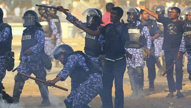 Police officers throw tear gas canisters during a clash with the military in Male, Maldives (AP)