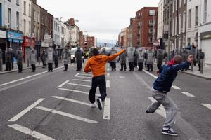 Protesters throw missiles at Irish police in the streets adjacent to the Garden on Remembrance where Queen Elizabeth II laid a wreath on May 17, 2011 in Dublin, Ireland.