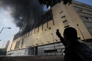 An Egyptian man uses his mobile phone to take a picture of the Arcadia shopping center, that was looted, damaged and set on fire by people in Cairo, Egypt, Sunday Jan. 30, 2011. (AP Photo/Lefteris Pitarakis)