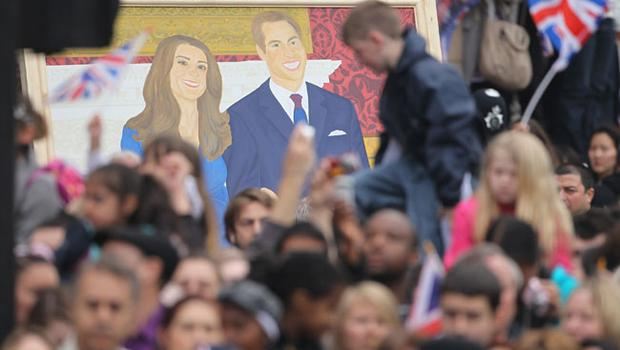 LONDON, ENGLAND - APRIL 29:  Someone carries a painting of Prince William and Catherine Middleton behind spectators along the procession route near Westminster Abbey on the day of the Royal Wedding on April 29, 2011 in London, England. The marriage of the second in line to the British throne is to be led by the Archbishop of Canterbury and will be attended by 1900 guests, including foreign Royal family members and heads of state. Thousands of well-wishers from around the world have also flocked to London to witness the spectacle and pageantry of the Royal Wedding.  (Photo by Sean Gallup/Getty Images)