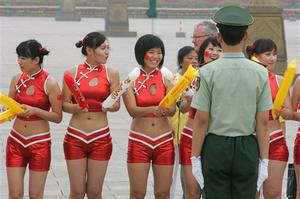 A paramilitary policeman watches over cheerleaders as they wait for the Olympic flame to arrive in Tiananmen Square during the Beijing Olympic Torch Relay in Beijing Wednesday Aug. 6, 2008.
