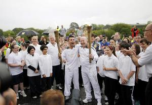 Olympic gold medal winning boxer Michael Carruth (right) receives the flame from Olympic silver medal winner Wayne McCullough (left) during the ceremony to hand over the Olympic Torch at the border crossing between the Republic of Ireland and Northern Ireland on Day 19 of the Olympic torch relay.