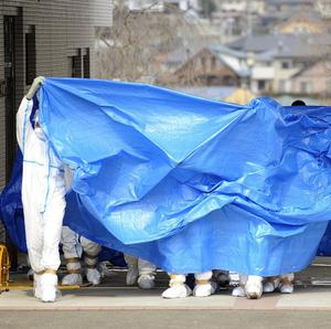 Workers who stepped into radiation-contaminated water are shielded with tarps before being decontaminated (AP Photo/Kyodo News)