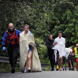 Medics and emergency workers escort youths from the island of Utoya (AP)