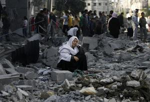 A Palestinian woman sits in rubble following an Israeli air strike in Rafah refugee camp in southern Gaza Strip, Sunday, Nov. 18, 2012. An Israeli envoy held talks with Egyptian officials Sunday on a ceasefire in his country's offensive on Gaza as Israel widened the range of its targets, striking more than a dozen homes of Hamas militants and two media officials. (AP Photo/Eyad Baba)