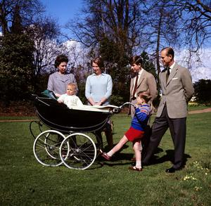21/04/1965 Prince Andrew at the handle of the pram rocks Prince Edward, watched by (left to right) his mother, Queen Elizabeth II, Princess Anne, the Prince of Wales, and his father, the Duke of Edinburgh. PRESS ASSOCIATION Photo.