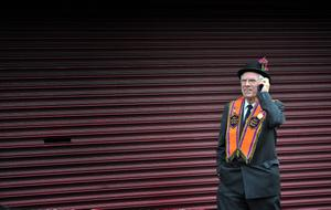 12/7/2012. An orangeman stands talking on his mobile phone at Carlise Circus in Belfast awaiting the start of the annual Orange 12th of July marches across the province. Picture Charles McQuillan/Pacemaker.