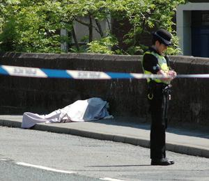 A Police officer stands guard beside an unidentified body on Bridge Road on June 02, 2010 in Whitehaven, England