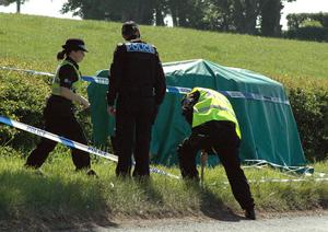 Police officers cordon off an area where an unidentied body lies on the road side verge on June 02, 2010 in the Seascale area, England