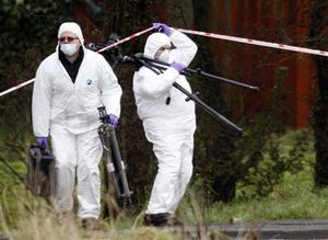 Police forensic officers attend the shooting scene near Lismore Manor, Craigavon, Northern Ireland, Tuesday, March 10, 2009. Irish Republican Army dissidents fatally shot a policeman in the head as he responded to an emergency call, just 48 hours after the killing of two soldiers, Northern Ireland's police commander said Tuesday. (AP Photo / Peter Morrison)
