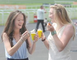 Alice Kavanagh, right from Monastervin, Co. Kildare and Ella Weld from Newbridge, Co. Kildare enjoy some ice cream at the Curragh races. May 2010