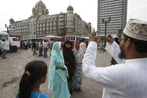 A family takes photo as they visit the Taj Mahal hotel where Indian commandos had a severe operation against terrorists, in Mumbai, India, Saturday, Nov. 29, 2008. Indian commandos killed the last remaining gunmen holed up at a luxury Mumbai hotel Saturday, ending a 60-hour rampage through India's financial capital by suspected Islamic militants that killed people and rocked the nation. (AP Photo/Saurabh Das)