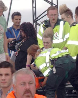 Edward Grimes of  seen being taken away to a waiting ambulance, with his left leg secured in a brace, after falling off stage during a performance of Ghostbusters at T4 on the beach.  Pictures: VIPIRELAND.COM