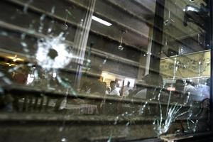 People are reflected in a mirror with bullet holes at Cafe Leopold, one of the several places where terrorists shot at people, after it reopened in Mumbai, India, Monday, Dec. 1, 2008. (AP Photo/Altaf Qadri)