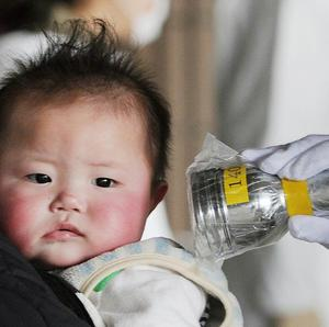 A baby is screened at an evacuation centre for leaked radiation from the damaged Fukushima nuclear plant