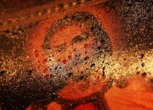 NEWTOWN, CT - DECEMBER 17:  Raindrops rest on a Jesus painting at a memorial for victims of the mass shooting at Sandy Hook Elementary School, on December 17, 2012 in Newtown, Connecticut. The first two funerals for victims of the shooting were held today.  (Photo by Mario Tama/Getty Images)