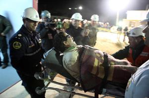 In this photo released by the Chilean government, Bolivian miner Juan Illanes is carried away on a stretcher after being rescued from the collapsed San Jose gold and copper mine where he was trapped with 32 other miners for over two months near Copiapo, Chile, early Wednesday Oct. 13, 2010.  (AP Photo/Hugo Infante, Chilean government)