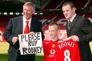 File photo dated 01/09/2004 of Manchester United manager Sir Alex Ferguson (left) and new signing Wayne Rooney (right) with Joe Ruane  (c) who held a sign pleading for the club to sign Rooney