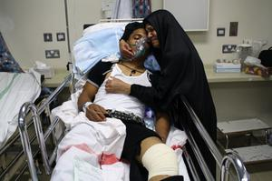 MANAMA, BAHRAIN - FEBRUARY 17:  A mother holds her injured son inside a hospital after at least three people died and hundreds were left injured when police stormed an anti-government protester camp in the capital's Pearl Square on February 17, 2011 in Manama, Bahrain. Police moved into Pearl Square overnight using batons and tear gas to clear protesters from their makeshift camp, resulting in fatalities and a large number of casualties.  (Photo by John Moore/Getty Images)