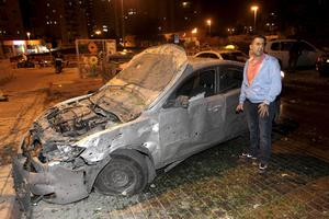 ISRAEL OUT - An Israeli man stands next to a car damaged by a rocket fired by Palestinian militants from the Gaza Strip in the southern Israeli city of Beersheva. Wednesday, Nov. 14, 2012.  (AP Photo/Ilan Assayag)