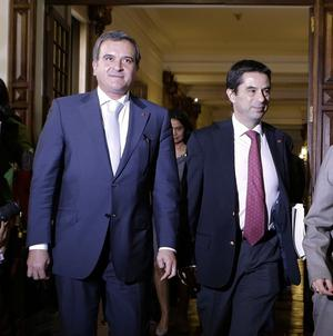 Portuguese Finance Minister Vitor Gaspar, right, and Parliamentary Affairs Minister Miguel Relvas arrive at parliament to deliver the draft budget (AP)