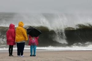 CAPE MAY, NJ - OCTOBER 28: People stand on the beach watching the heavy surf caused by the approaching Hurricane Sandy, on October 28, 2012 in Cape May, New Jersey. Hurricane Sandy is expected to hit the New Jersey coastline sometime on Monday bringing heavy winds and floodwaters.  (Photo by Mark Wilson/Getty Images)