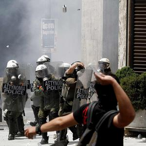 A demonstrator throws stone at police in Athens (AP)