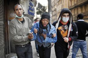 Two Egyptian protesters accompany a man, center, overcome with tear gas inhalation during the clashes with Egyptian riot police, unseen, in Tahrir square, Cairo, Egypt, Monday, Nov. 21, 2011. Egyptian riot police clashed Monday with thousands of protesters demanding that the ruling military quickly announce a date to hand over power to an elected government.  (AP Photo/Mohammed Abu Zaid)