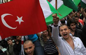 Pro-Palestinian demonstrators hold a Turkish national flag and shout anti-Israel slogans during a protest in the Bulgarian capital Sofia, Tuesday, June, 1, 2010