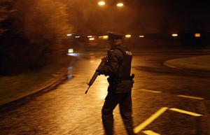 A Police Service of Northern Ireland officer takes up position near Lismore Manor, Craigavon, Northern Ireland, Tuesday, March 10, 2009. A large security presence has begun after a Police Service of Northern Ireland officer was shot dead by suspected Irish Republican terrorists.  (AP Photo/Peter Morrison)