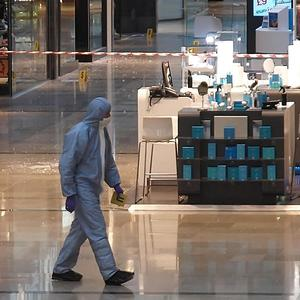 A forensics officer attends the scene at Westfield in Stratford, east London, after a man was stabbed to death.