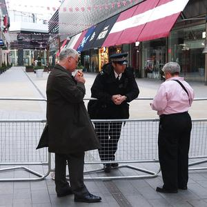 A police officer explains to passers-by why areas are cordoned off at Westfield in Stratford, east London, after a man was fatally stabbed