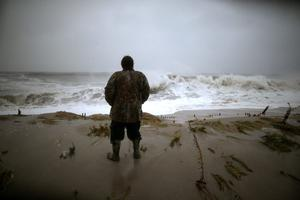 CAPE MAY, NJ - OCTOBER 29:  Andy Becica stands on the beach watching the heavy surf from Hurricane Sandy wash in in, on October 29, 2012 in Cape May, New Jersey. Later today the full force of Hurricane Sandy is expected to hit the New Jersey coastline bringing heavy winds and floodwaters.  (Photo by Mark Wilson/Getty Images) *** BESTPIX ***