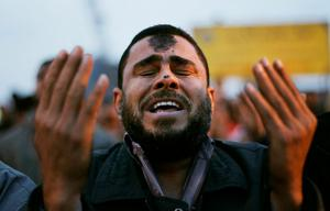 CAIRO, EGYPT - JANUARY 30:  An anti-government protester cries during Islamic prayers in Tahrir Square at sundown January 30, 2011 in Cairo, Egypt. Cairo remained in a state of flux and marchers continued to protest in the streets and defy curfew, demanding the resignation of Egyptian president Hosni Mubarek. As President Mubarak struggles to regain control after five days of protests he has appointed Omar Suleiman as vice-president. The present death toll stands at 100 and up to 2,000 people are thought to have been injured during the clashes which started last Tuesday. Overnight it was reported that thousands of inmates from the Wadi Naturn prison had escaped and that Egyptians were forming vigilante groups in order to protect their homes.   (Photo by Chris Hondros/Getty Images)