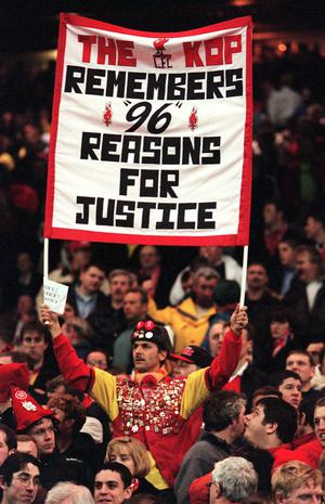 A Liverpool supporter holding a banner