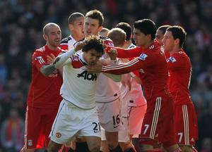 Rafael of Manchester United is restrained following his challenge on Lucas of Liverpool during the Barclays Premier League match between Liverpool and Manchester United at Anfield on March 6, 2011 in Liverpool