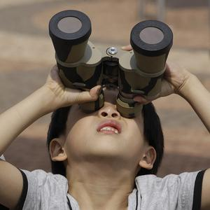 A boy uses a pair of binoculars with special filters to observe the transit of Venus in South Korea (AP/Lee Jin-man)