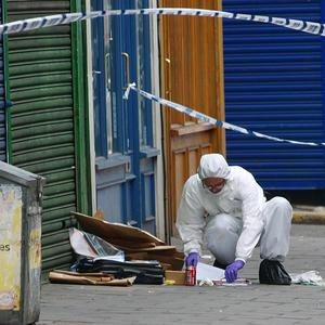 A forensic expert searches the scene of a shooting on Waylett Place, West Norwood, south London where a 20 year-old man was shot dead
