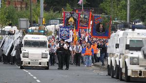 Police accompany the Orange Order parade past the Ardoyne shops in north Belfast