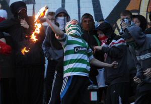 Nationalist youths clash with riot police before an Orange Order  parade passes the Ardoyne shops in north Belfast