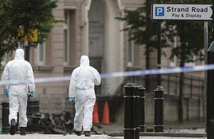 PSNI officers investigate the car bomb which exploded at Short Strand PSNI station. August 2010